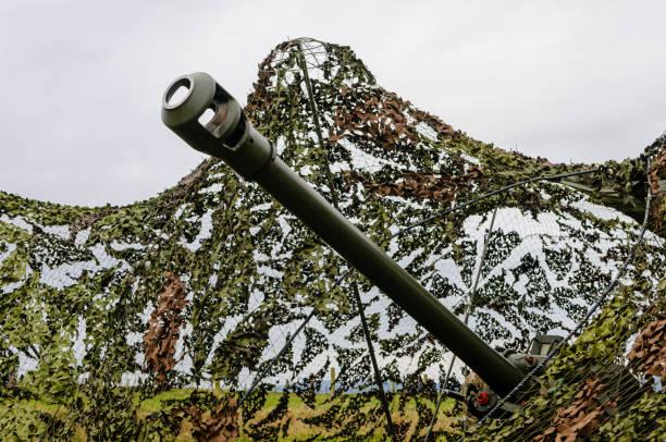 Schnauze einer Haubitze Leichte Artillerie Gun stochert durch Tarnnetz in einem Feld – Foto