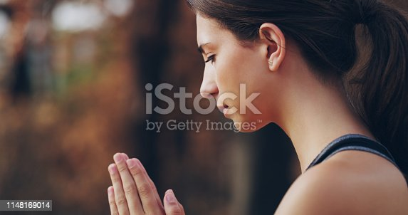 Shot of a sporty young woman standing with her hands clasped