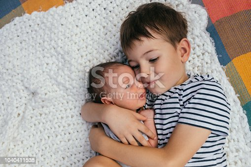 Portrait of a loving brothers: an elder one is hugging his newborn baby brother