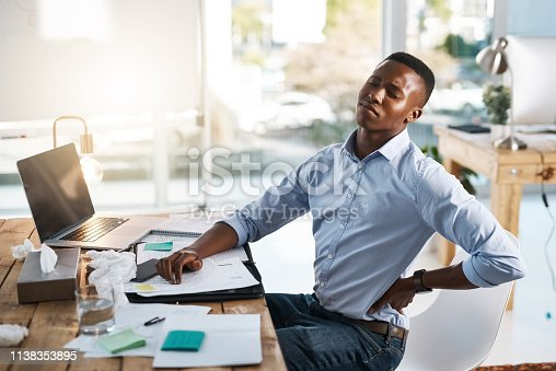 Shot of a young businessman suffering from back pain while trying to work in the office