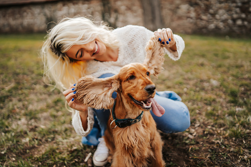 Joyful young woman hugging and playing with her dog outdoors
