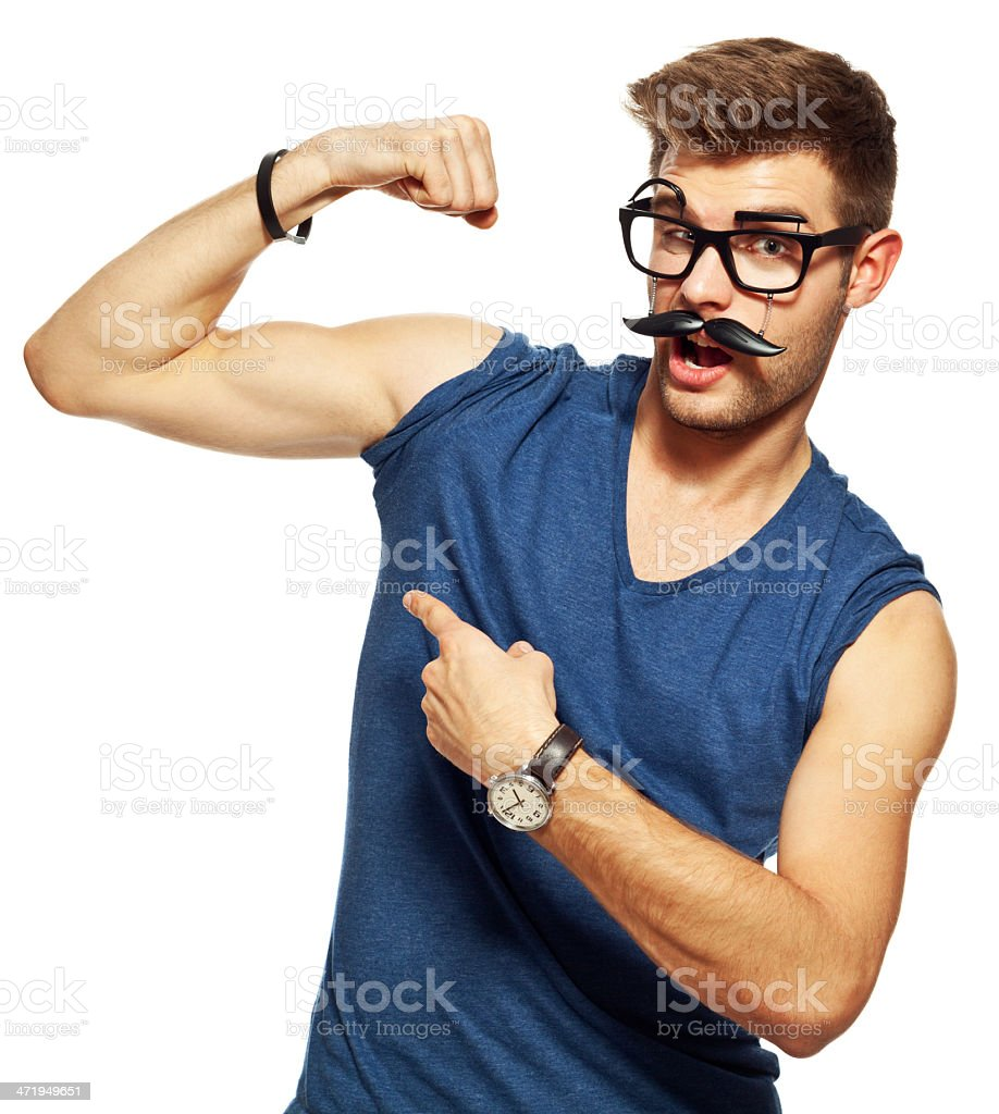 My biceps! Portrait of confident young man wearing funny face mask showing his biceps. Studio shot, white background. 20-29 Years Stock Photo