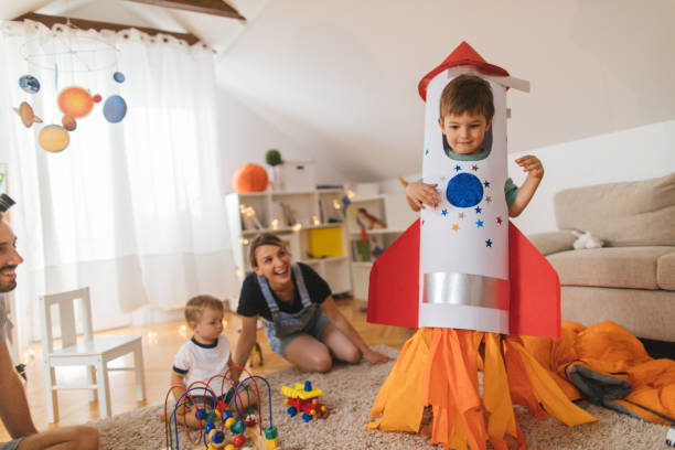 My big brother is a rocket! Photo of a young family spending time together indoors, playing with their two boys and getting costume ready for the Halloween costume stock pictures, royalty-free photos & images
