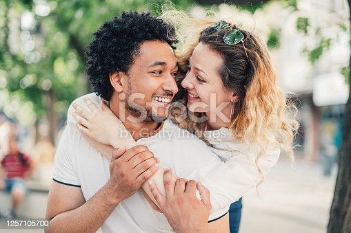 Portrait of a young beautiful multi-ethnic couple smiling and looking each other.