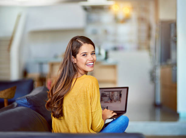 My blog is getting tons of traffic Portrait of an attractive young woman using a laptop while relaxing on the sofa at home looking over shoulder stock pictures, royalty-free photos & images
