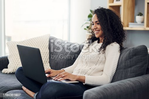 Cropped shot of an attractive young woman using a laptop while relaxing on her couch at home