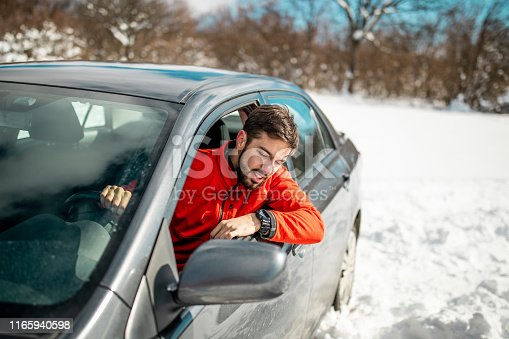 Man is stuck with his car in the deep snow