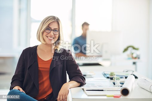 Portrait of a young woman working at her desk in a modern office
