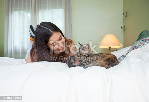 Girl with her cat on the bed
