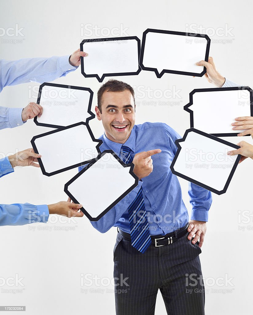My choice Portrait of happy businessman surrounded by many speech bubbles with copyspace and pointing at one of them. Smiling at the camera. 30-34 Years Stock Photo