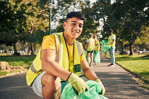 Cropped portrait of a young male volunteer doing community service in the local park with his friends in the background