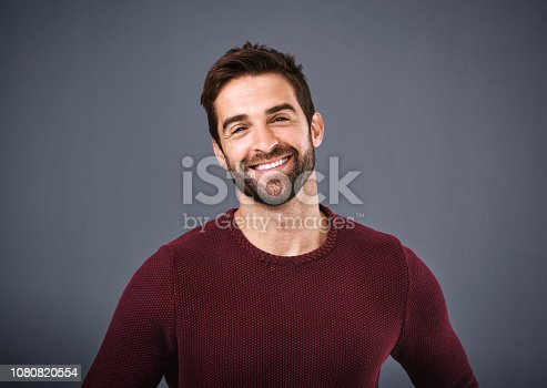 Studio shot of a handsome and happy young man posing against a gray background