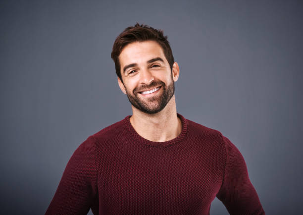 My confidence comes naturally Studio shot of a handsome and happy young man posing against a gray background charming stock pictures, royalty-free photos & images