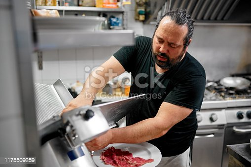 Shot of a chef preparing a dish in the kitchen of a restaurant