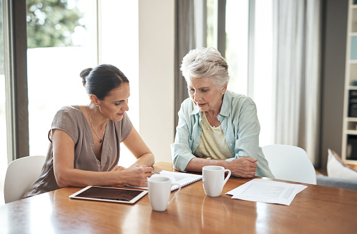 Cropped shot of an attractive young woman assisting her elderly mother with her finances at home