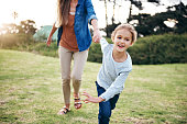 Shot of an adorable little girl holding her unrecognizable mother's hand outdoors