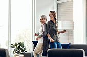 Shot of a senior woman and her adult daughter dancing together at home