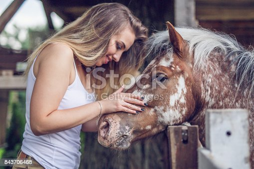 A happy girl storking her horse
