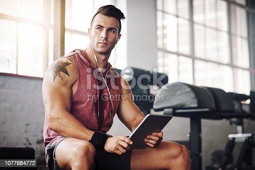 Cropped shot of a handsome young man using a tablet at the gym