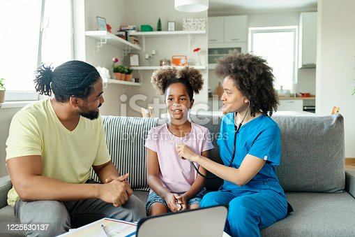 Female Pediatrician Doctor Examining a Little Girl by Stethoscope While Sitting on the Sofa in the Livingroom. Children Medical Insurance. Paediatrician Visiting Client at Home. Medical Exam, Pediatry and Healthcare Concept