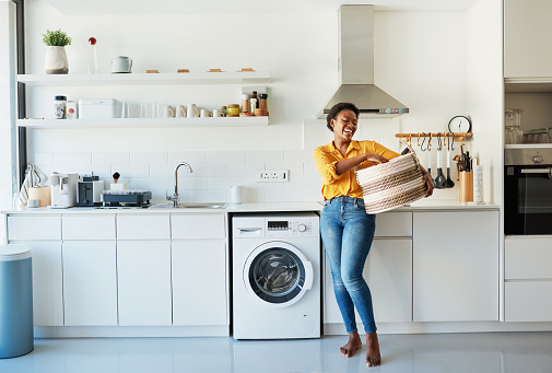 Shot of a young woman doing her laundry at home