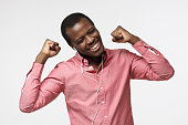 istock My favourite song. Young happy black man smiling, listening music via headphones, dancing with closed eyes isolated on gray background. 997616798