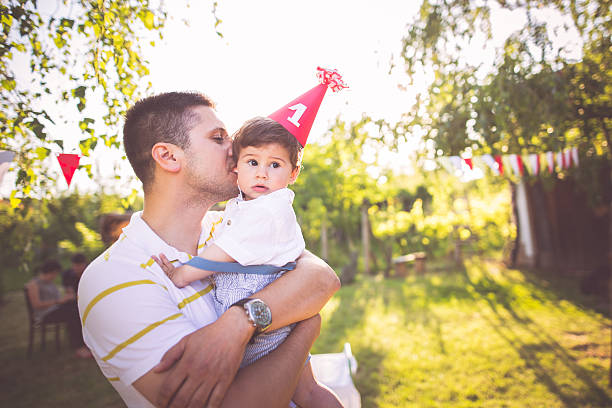 My first birthday Photo of father and son in the embrace first birthday stock pictures, royalty-free photos & images