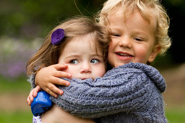 my first kiss - harassment - little girls little boys kissing love stock photos and pictures