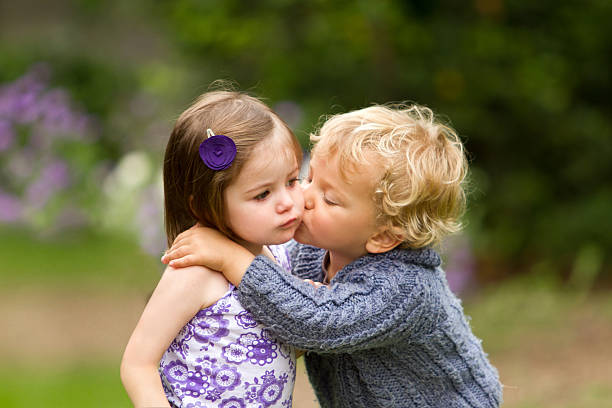 my first kiss - little girls little boys kissing love stock photos and pictures