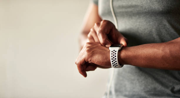 My fitness tracker motivates me to be more active Cropped shot of an unrecognizable man checking his wristwatch medical technology stock pictures, royalty-free photos & images