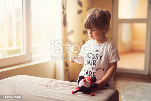 cute little girl measured temperature on her fluffy toy friend with thermometer.
