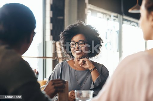 Shot of an attractive young woman sitting and smiling with her friends in a coffee shop during the day