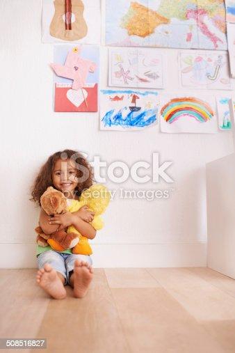 Portrait of a cute little girl hugging her stuffed animals