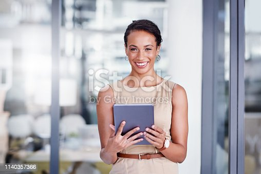Portrait of a young businesswoman using a digital tablet in a modern office