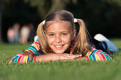 My hair my look. Happy child with beauty look relax on green grass. Vogue look of small fashion model. Adorable girl smile with fashion look on summer day.