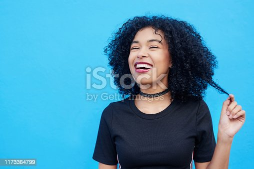 Shot of an attractive young woman pulling her hair against a blue background