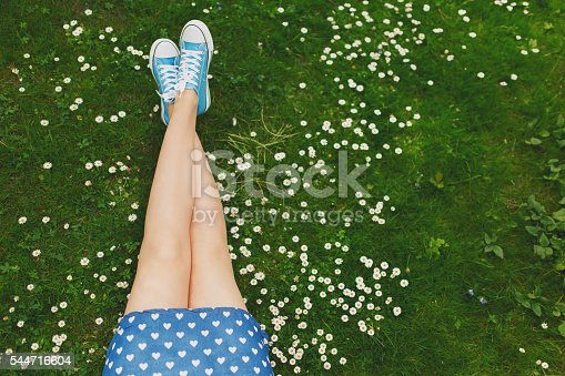 Unrecognizable female sitting on a green grass among daisies, enjoying a carefree summer day at the park.