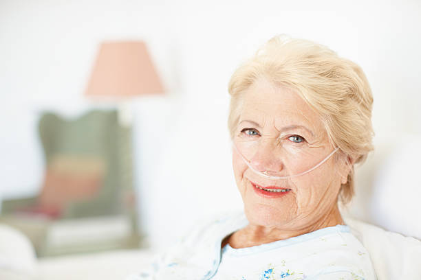 My health insurance is taking care of everything! Portrait of an elderly woman wearing a nasal cannula lying in hospital bed - Copyspace medical oxygen equipment stock pictures, royalty-free photos & images
