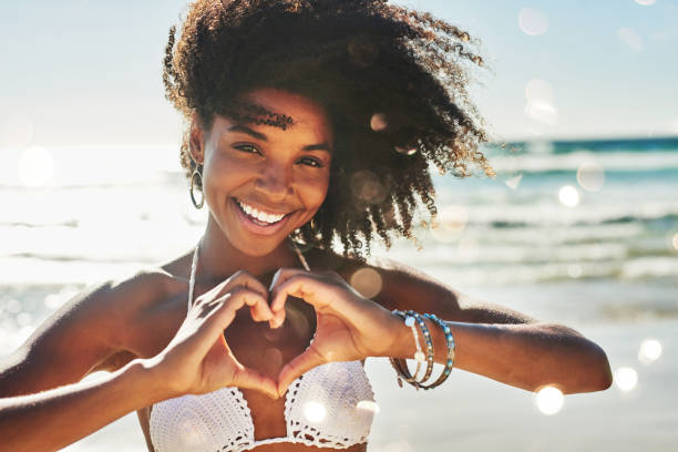 My heart belongs to summer Portrait of a beautiful young woman making a heart shaped gesture with her hands at the beach bikini stock pictures, royalty-free photos & images