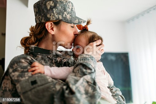 Military mom hugging with her child, little baby girl. Mother kissing her little girl. Having some happy time together. Mother just return from some of army missions.