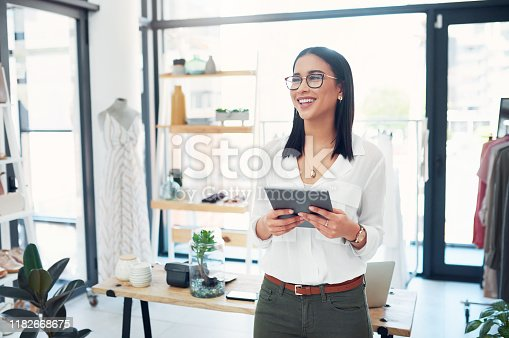 Cropped shot of a young business owner using her tablet while standing in her store