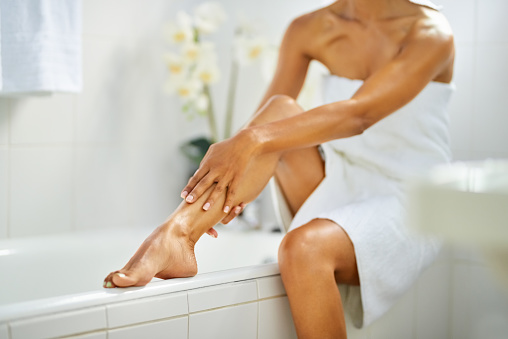 Cropped shot of a woman in bathrobe sitting on bathtub and touching her leg