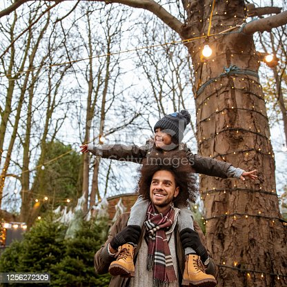 A mixed-race father and son at a Christmas tree farm together in Newcastle-Upon-Tyne. The man is carrying the boy on his shoulders, who has his arms outstretched. They are both looking away from the camera.