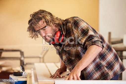 Shot of a man working with wood in a furniture manufacturing workshop