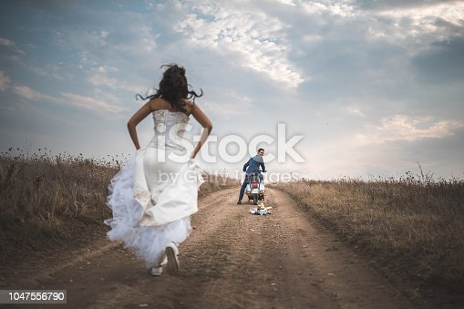 Bride running towards the bridegroom who is waiting her on the vespa motorbike to go away somewhere