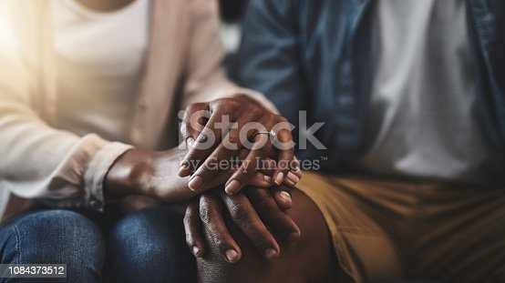 Cropped shot of a man and woman sitting on a sofa and holding hands