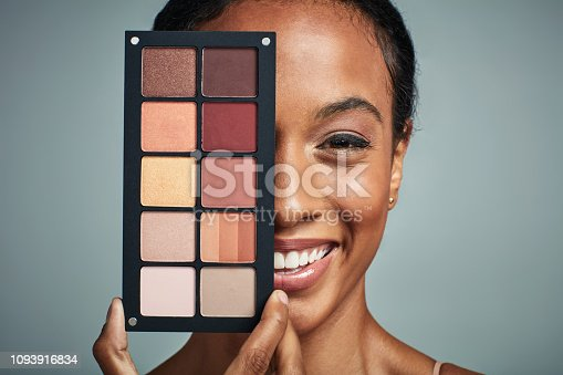 Studio shot of a beautiful young woman holding a make up palette against a grey background