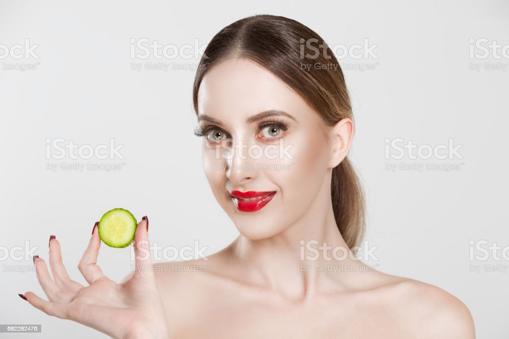 My mask is tasty. Woman showing cucumber slice looking at you camera smiling isolated white background stock photo