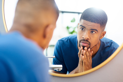 Shot of young man admiring his face in his bathroom mirror