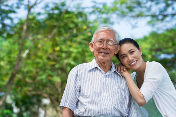 My old dad Portrait of happy senior man and his adult daughter leaning on his shoulder vietnamese ethnicity stock pictures, royalty-free photos & images
